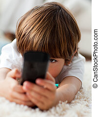 Adorable little boy holding a remote lying on the floor