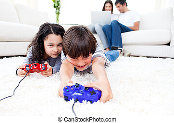 Excited children playing video games lying on the floor