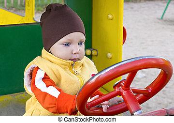 One year boy in toy car