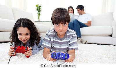 Children playing video games lying on the floor