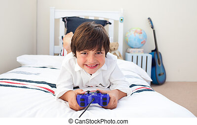 Cute little boy playing video games in his bedroom