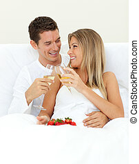 Intimate couple drinking Champagne with strawberries lying...