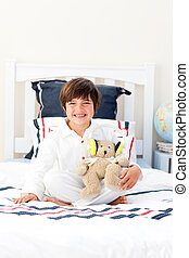 Smiling little boy playing with a teddy bear