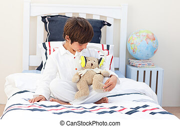 Beautiful little boy playing with a teddy bear in his bedroom