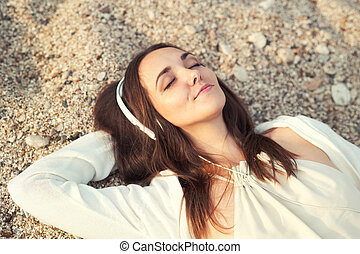 Woman lying on a sea sand and listening music. - Smiling...