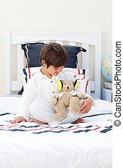 Cute little boy playing with a teddy bear