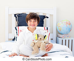 Positive little boy playing with a teddy bear in his bedroom