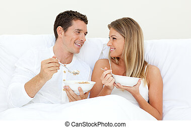 Affectionate couple having breakfast lying on their bed
