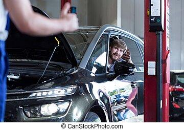 Driver in auto repair shop - Picture of happy driver in auto...