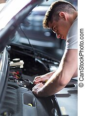 Auto mechanic fixing car - Portrait of young busy auto...