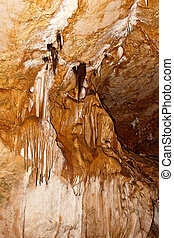 Stalactite and stalagmite formations on the wall of an underground cave.