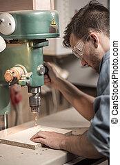 Carpenter using a drill machine - Carpenter in goggles using...