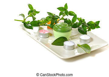 aromatherapy - scented candles and green leaves on white...