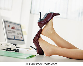 business woman taking off shoes in office