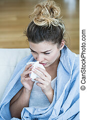 Feverish woman with tissue blowing the nose
