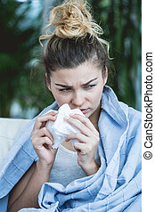 Ill woman with tissue blowing the nose