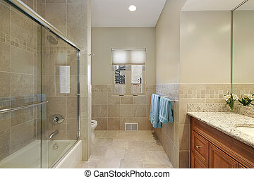 Master bath with blue towels and glass shower