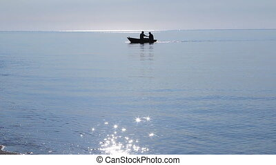Fishermen in a boat floating to the shore in the morning...