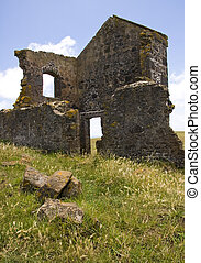 Ruin of house on hill against sky.