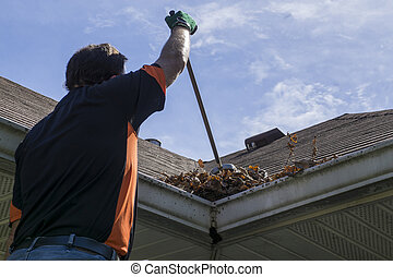 Worker Sweeping Leaves From Roof Valley - Worker sweeping...