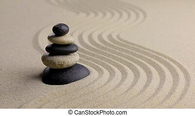 Stones pyramid on sand symbolizing zen, harmony, balance,motion,