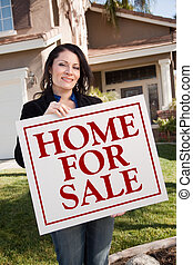 Woman Holding Home For Sale Real Estate Sign In Front of House
