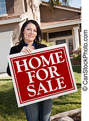 Hispanic Woman Holding Real Estate Sign In Front of House -...