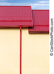 metal drainpipe fixed on wall - new red tiled roof of new...