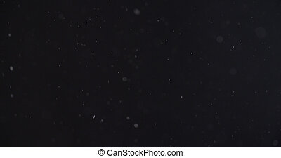 abstract particles flying over black background,dust snow or...
