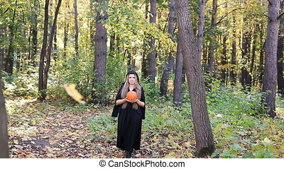 beautiful witch with a pumpkin in autumn forest