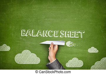 Balance sheet concept on blackboard with paper plane -...