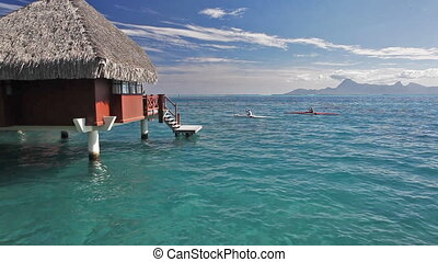 Man on kayaks next to over water bungalow