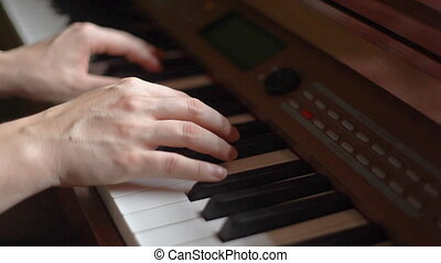 Hands of young woman playing piano
