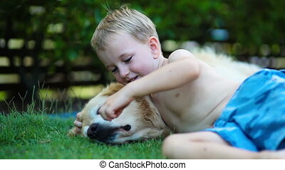Young boy and his golden retriever in the grass