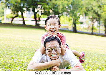 happy father and little girl lying on the grass