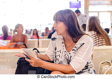 Woman checking her passport in an airport terminal as she...