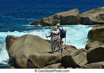elderly couple standing back on the beach