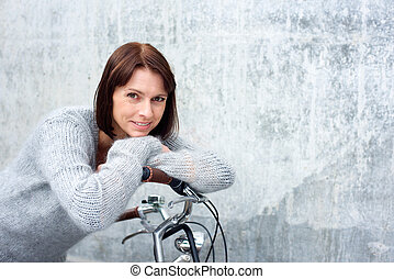 Attractive older woman smiling with bike - Close up portrait...