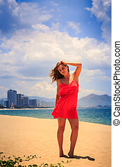 blond girl in red stands on beach smooths shaken by wind...
