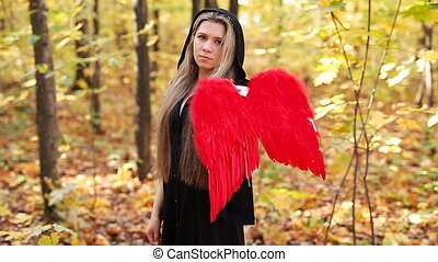 Beautiful girl with red angel wings in forest - Beautiful...