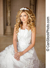 Portrait of a beautiful smiling bride in white wedding dress. Young woman with long curly hair style and makeup, sitting on sofa at wedding day. modern style.