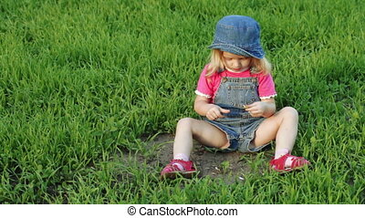 Child on lawn with flower - On lawn girl child guesses on...