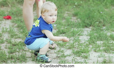 Boy at feet of mothers - One year old boy holding his...