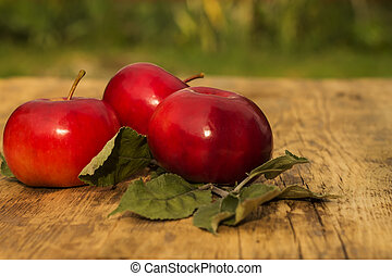 Three red apples with leaves on a blurred background