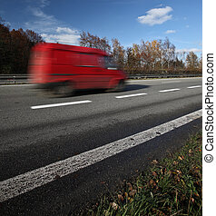 Red deliverycargo van going fast on a highway