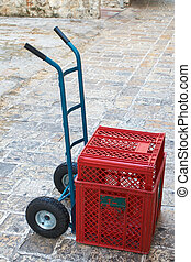 Trolley with plastic crates on old stone road
