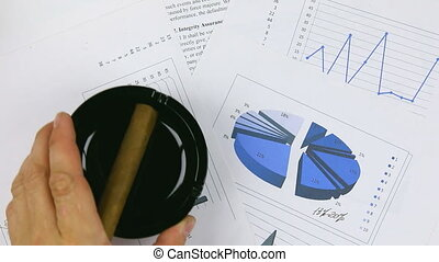 Businessman puts a black ashtray and cigar on chart, a top...