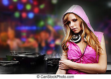 Beautiful DJ girl in pink standing in the front of the decks...