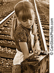 Sepia Sad - Young girl with vintage suitcase on railroad...