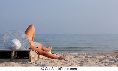 Young girl lying on a beach lounger with sand in the hand on...